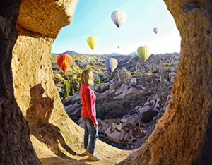 Woman with shadow watching colorful hot air balloons fly in the distance